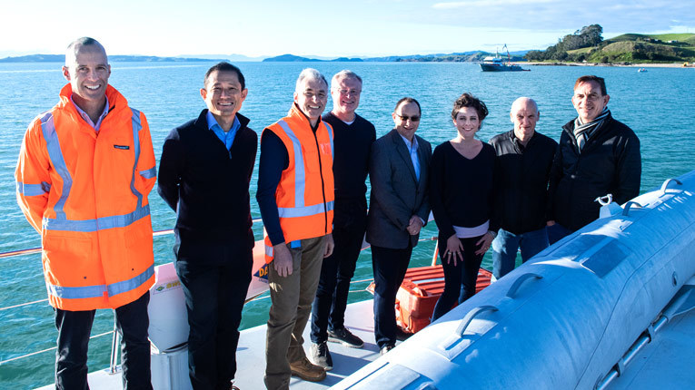 Team members in New Zealand by the water