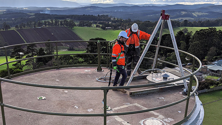 Two individuals in high-vis attire repairing water tank in Gembrook